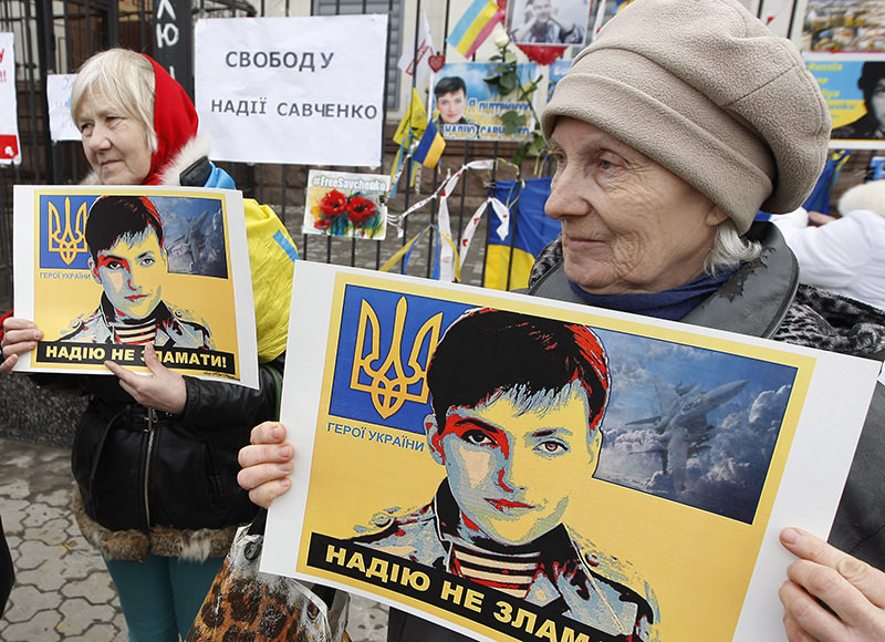 Women holds posters depicting Ukrainian pilot Nadezhda Savchenko outside the Russian Embassy in Kiev, Ukraine, Tuesday, March 22, 2016. (AP Photo)