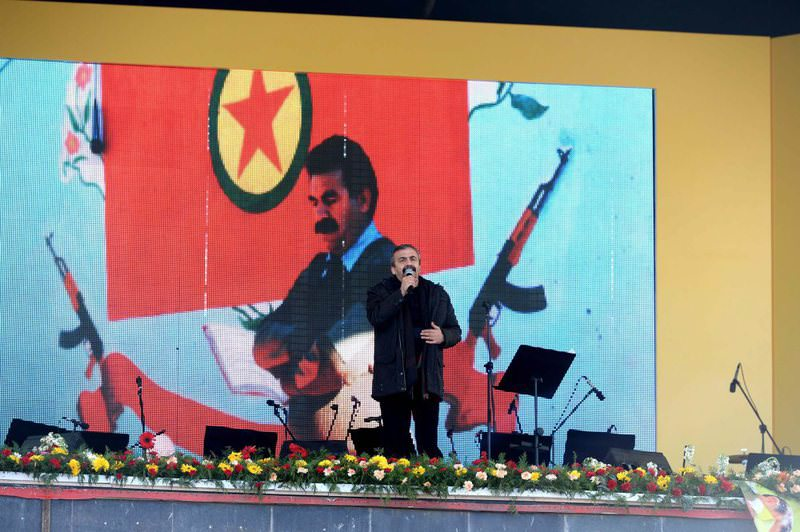 HDP Ankara Deputy u00d6nder addressing a crowd at an HDP gathering in Diyarbaku0131r province on Monday in front of images of weapons, imprisoned PKK leader u00d6calan and a PKK flag.