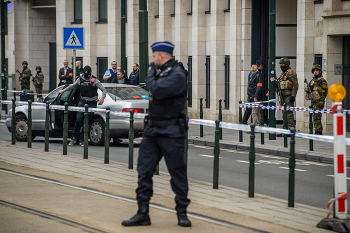 Police officers stand guard outside the court where suspect Salah Abdeslam (non pictured) is expected to make an appearance, in Brussels, Belgium, 24 March 2016 (EPA Photo)