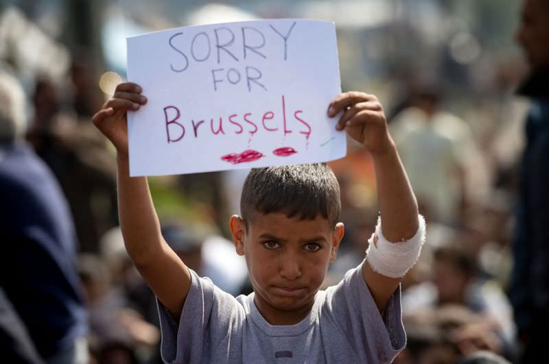 A migrant boy holds a placard expressing sympathy for the victims of the terror attacks in Brussels during a protest at a makeshift camp at the Greek-Macedonian border near the village of Idomeni on March 22.