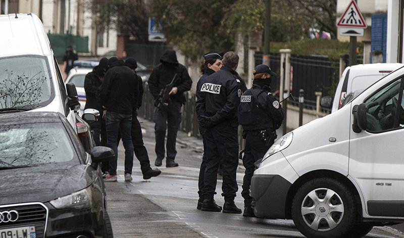 Police officers and investigators stand outside a building where an anti-terrorism operation took place in Argenteuil, near Paris, 25 March 2016 (EPA Photo)