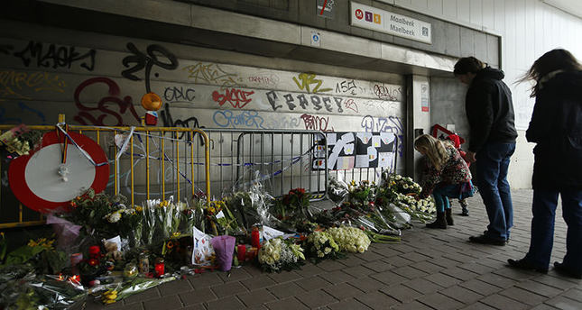 People stop, look at floral tributes placed outside the Maelbeek metro station, the scene of one of the bomb attacks on the Belgian capital, in Brussels, March 26, 2016 AP