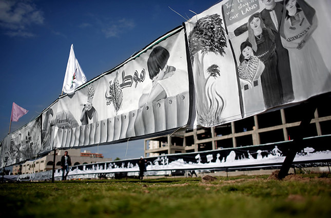 People walk past large banners made by Palestinian artists marking the 40th Land Day anniversary, in Gaza City, Wednesday, March 30, 2016 AP Photo