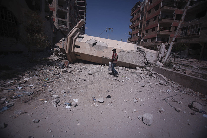A Syrian boy walks past the collapsed minaret of a mosque in the rebel-held city of Douma, outside Damascus, 31 March 2016 (EPA Photo)