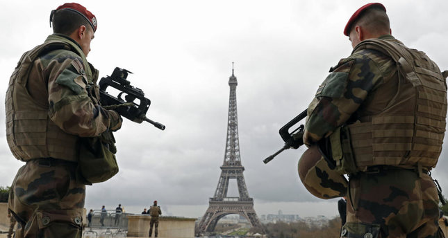 French paratroopers patrol near the Eiffel tower in Paris on March 30. France and Belgium have intensified their security measures in urban centers following terror attacks.