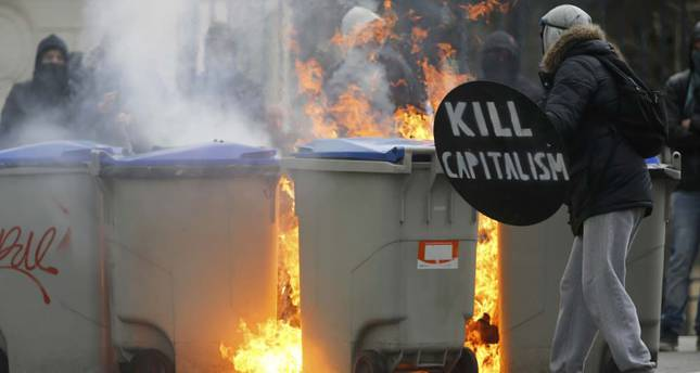 Masked demonstrators gather near burning garbage bins during clashes as French high school and university students attend a demonstration against the French labor law proposal in Nantes, France
