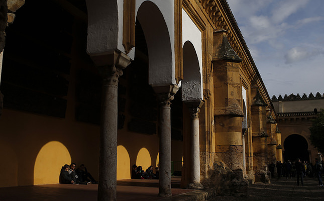 People rest as the shadow of arches light is cast on the wall behind them outside of the Mosque Cathedral of Cordoba, Spain, Monday, March 21, 2016. (AP Photo)