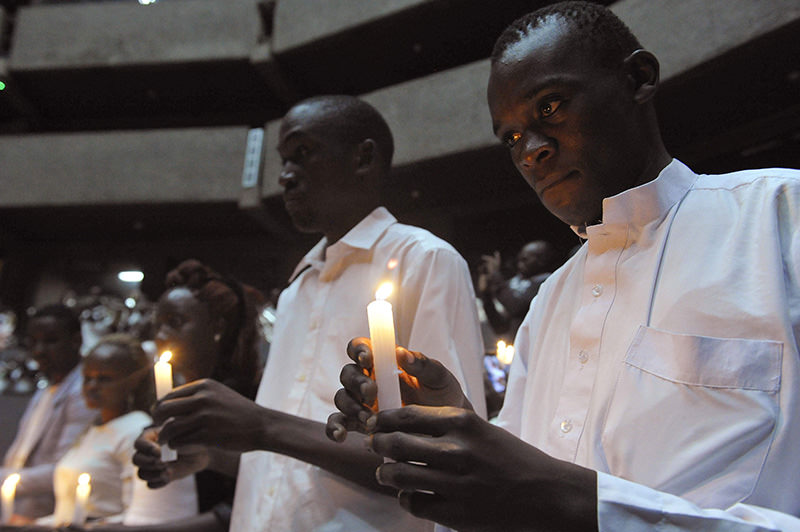 Former students of Garissa Univesity College hold candle on the memorial for the victims of last year's terrorist attack (AFP Photo)