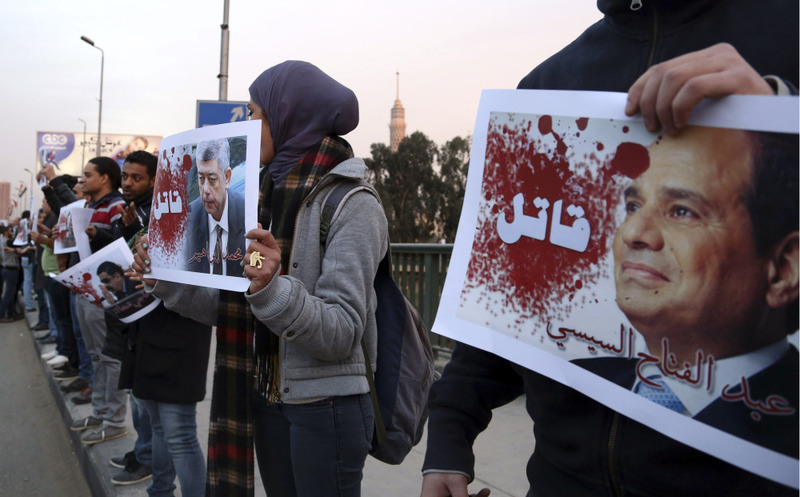 Protesters hold posters of Egyptian President el-Sissi (R) and Interior Minister Mohamed Ibrahim with the word ,Killer, during a silent protest on a bridge in Cairo on Feb. 14, 2015. (Reuters Photo)