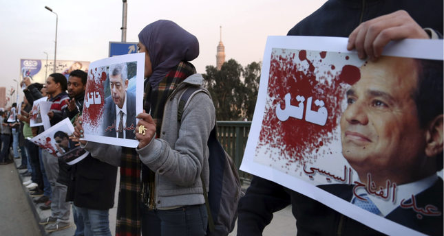 Protesters hold posters of Egyptian President el-Sissi R and Interior Minister Mohamed Ibrahim with the word Killer during a silent protest on a bridge in Cairo on Feb. 14, 2015. Reuters Photo