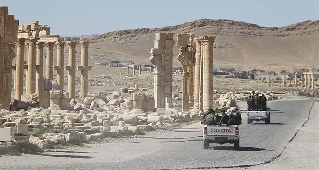Syrian army soldiers drive past the Arch of Triumph in the historic city of Palmyra, in Homs Governorate, Syria April 1, 2016 (Reuters)