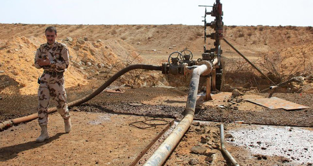 In this file photo provided on Sept. 9, 2015, a member of the regime forces inspects the Jazal oil field following battles with Daesh.