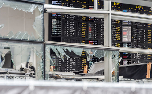 In this March 23, 2016 file photo, an arrivals and departure board is seen behind blown out windows at Zaventem Airport in Brussels. (AP Photo)