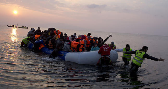 Volunteers help migrants on a dingy as they arrive at the shore of the northeastern Greek island of Lesbos, after crossing the Aegean sea from Turkey  March 20, 2016 (AP)
