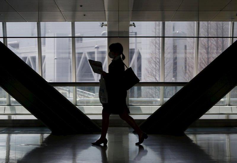 A female job seeker walks as she attends a job fair held for fresh graduates in Tokyo, Japan.