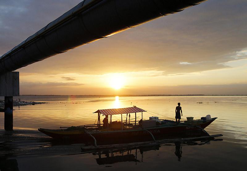 Filipino fishermen maneuver their boat as the sun sets in Manila Bay, Philippines, 01 April 2016. (EPA Photo)