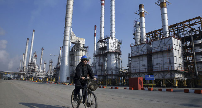An Iranian oil worker rides his bicycle at the Tehran oil refinery, south of the capital Tehran. Iran's oil exports have surpassed 2 million barrels per day as Tehran seeks to win back its pre-sanctions market share.