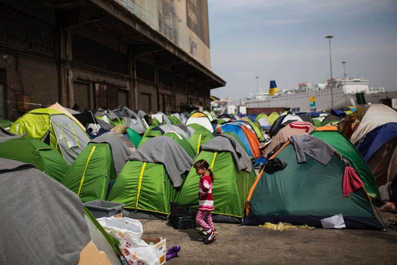A girl walking among tents outside a passenger terminal used as a shelter for refugees at the Piraeus harbour in Athens.