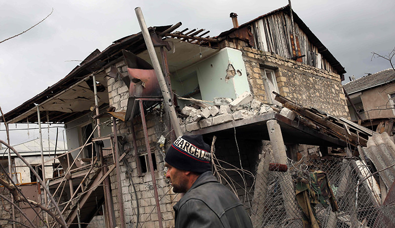 A picture taken on April 4, 2016 shows a man walking past a building, which was damaged during clashes between Armenian and Azeri forces over the Nagorny Karabakh region (AFP Photo)