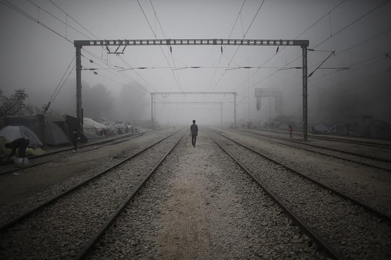 A refugee walks on the train tracks amidst morning mist at a refugee camp near the Greek-FYROM border near the village of Idomeni, northern Greece, 04 April 2016. (EPA Photo)