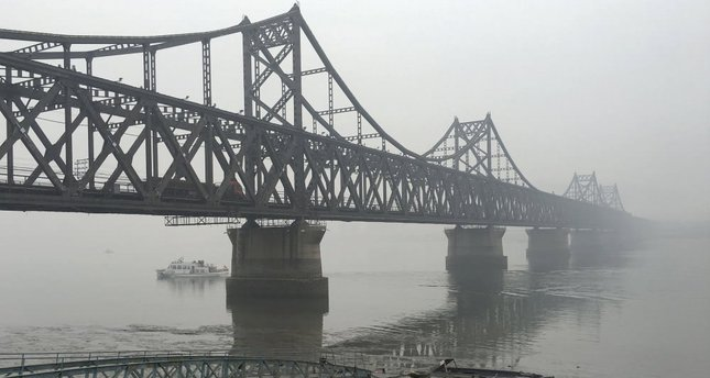 Trucks move across the bridge linking North Korea to the Chinese border city of Dandong in this March 3. file photo.