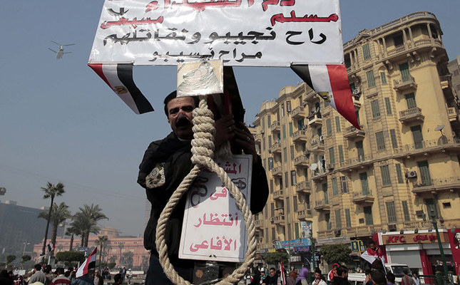 An pro-Sissi Egyptian holds a hanging rope and a poster reading in Arabic 'whether they are Muslims or Christians, we will avenge the blood of our martyrs', at Tahrir square, Cairo, Egypt, Jan. 25, 2014. (EPA Photo)