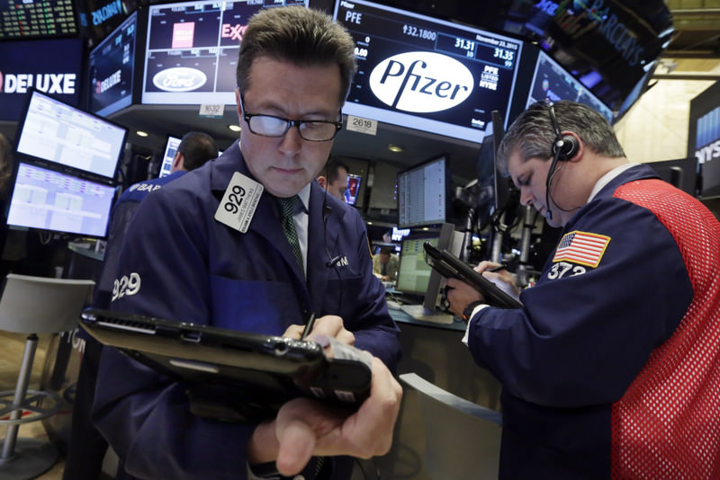 Traders work at the post that handles Pfizer on the floor of the New York Stock Exchange. Allergan and Pfizer yesterday called off a record $160 billion merger after the Treasury issued new rules to make ,tax inversions, less lucrative.