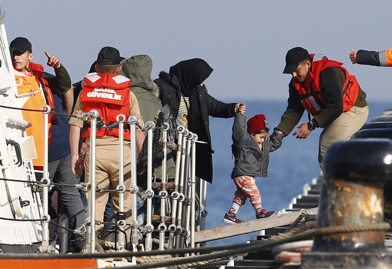 Turkish Coast Guard officials help migrants disembark from a Coast Guard vessel after their boat was intercepted en route to the Greek island of Lesbos.