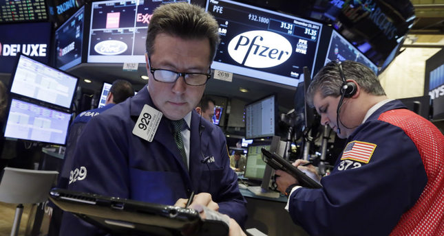 Traders work at the post that handles Pfizer on the floor of the New York Stock Exchange. Allergan and Pfizer yesterday called off a record $160 billion merger after the Treasury issued new rules to make tax inversions less lucrative.