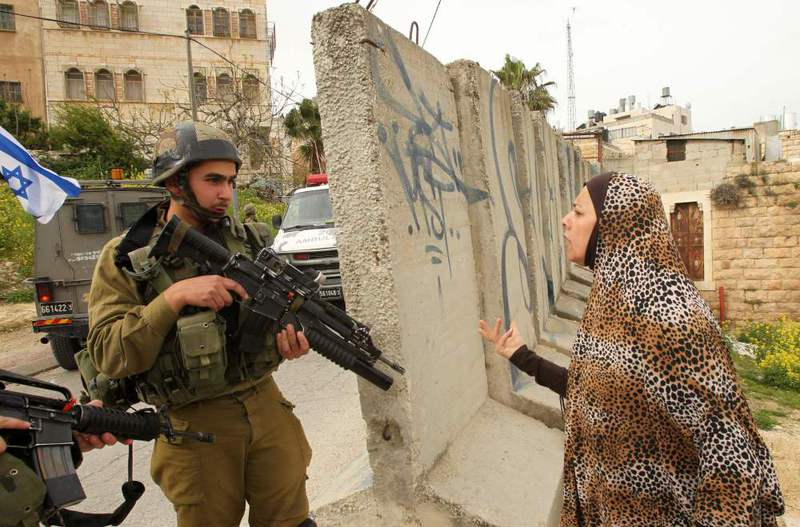 A Palestinian woman speaking with an Israeli soldier at the scene of an attack in which an Israeli soldier shot dead two Palestinians who were protesting against them, Hebron, Palestine.