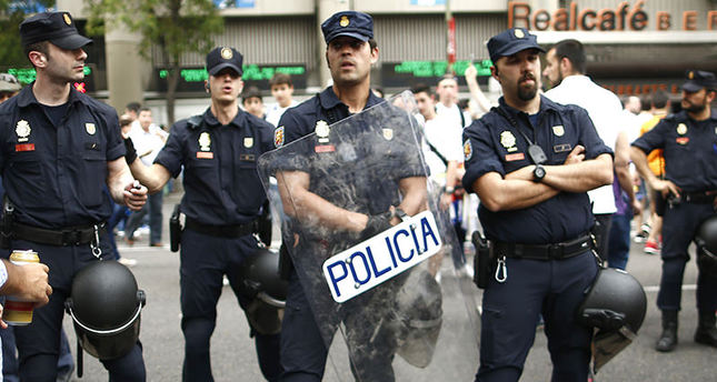 Police officers stand guard as soccer fans arrive for the Champions League second leg semifinal soccer match between Real Madrid and Juventus, at the Santiago Bernabeu stadium in Madrid (AP Photo)
