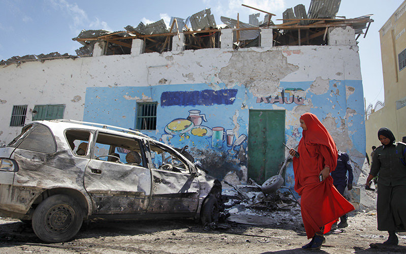 A female police officer inspects the scene of a car bomb attack outside a restaurant in the capital Mogadishu, Somalia Saturday, April 9, 2016. (AP Photo)