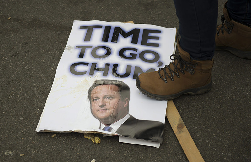 A protester steps on a placard with the picture of British Prime Minister David Cameron during a demonstration calling for Cameron's resignation in Central London. (EPA Photo)