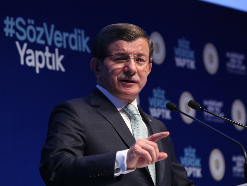 Prime Minister Davutou011flu speaks at the 2016 Action Plan meeting in Istanbul. In the background, is  the hashtag #Su00f6zVerdikYaptu0131k  (We promised, we did.)