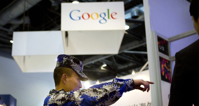 In this April 29, 2015, file photo, a security guard points while walking past a display booth for Google at the Global Mobile Internet Conference in Beijing.
