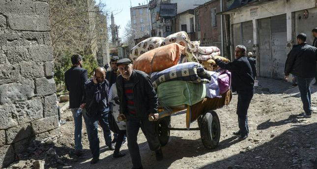 People carry their belongings on a cart as they return to their homes after clashes ended in the Sur district of Diyarbakır in southeast Turkey.