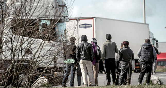Refugees stand looking at lorries stationed in a parking lot in Marck, just north of the sea port of Calais on the English Channel on March 30, 2016 (AFP)