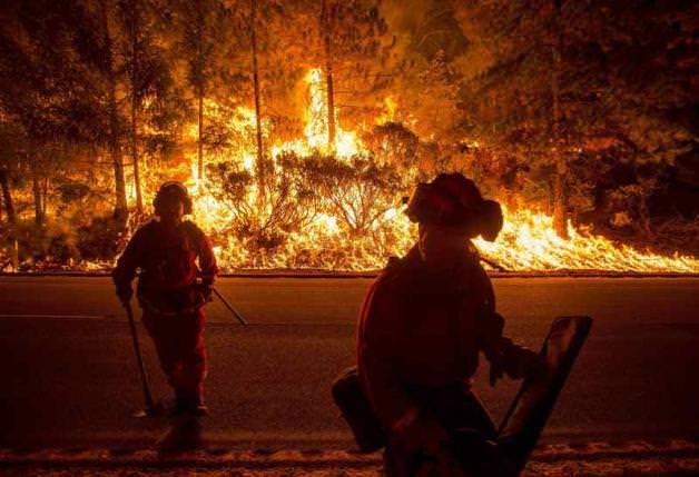 Firefighters battling the King Fire watch as a backfire burns along Highway 50 in Fresh Pond, California in this September 16, 2014 file photo. (REUTERS Photo)