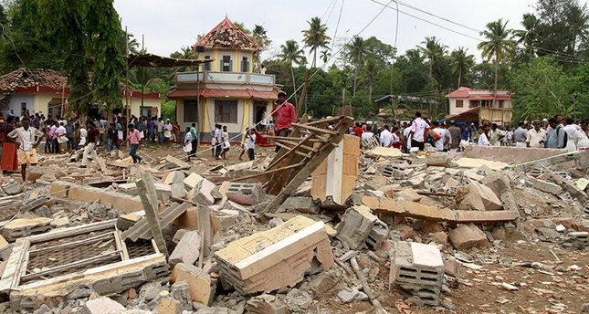 People stand next to debris after a broke out at a temple in Kollam in the southern state of Kerala, India. Reuters Photo