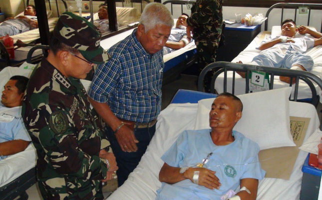 The Philippines Defense Minister Voltaire Gazmin (C) and Chief of General Staff Hernando Iriberri (L) visit soldiers at a Mindanao hospital who were wounded in the clashes against Abu Sayyaf group. (AA Photo)