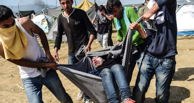 Refugees carry a man injured during clashes with Macedonian soldiers near their makeshift camp in the northern Greek border village of Idomeni, on April 10, 2016. (AFP Photo)