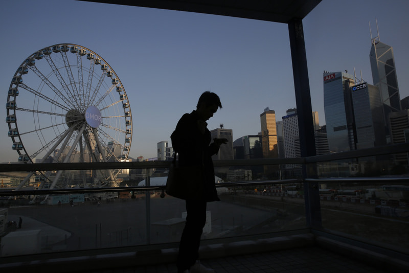 A man uses his smartphone in Central, a business district of Hong Kong.