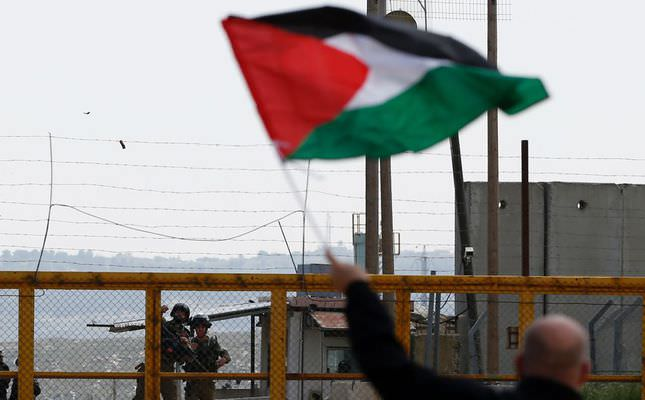 A Palestinian man waving his national flag in front of Israeli soldiers as they mark Land Day outside the compound of the Israeli-run prison in the Israeli occupied West Bank.
