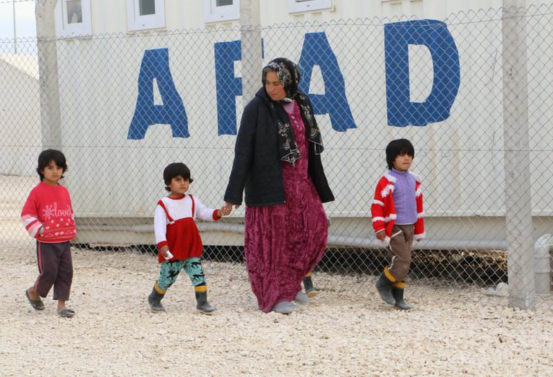 A woman and three children walk past a Disaster and Emergency Management Authority (AFAD) container in the city of u015eanlu0131urfa, which hosts the largest number of Syrian refugees in Turkey and the world.