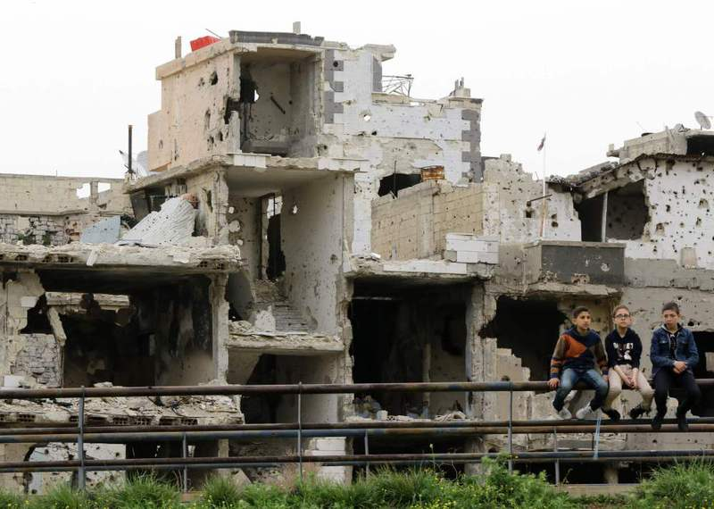 Displaced young Syrian boys siting on a railing in front of heavily damaged buildings in the central Syrian city of Homs