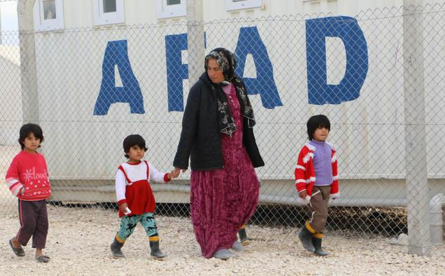 A woman and three children walk past a Disaster and Emergency Management Authority (AFAD) container in the city of Şanlıurfa, which hosts the largest number of Syrian refugees in Turkey and the world.
