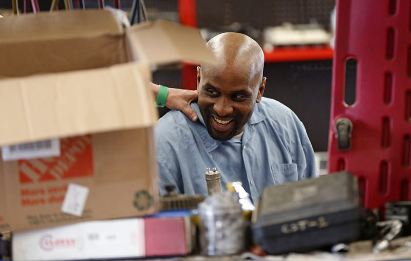 In this March 23, 2016 photo, Rickey Arvie, HVAC mentor, gets a pat on the back by a mentee in the auto repair training shop. (AP Photo)