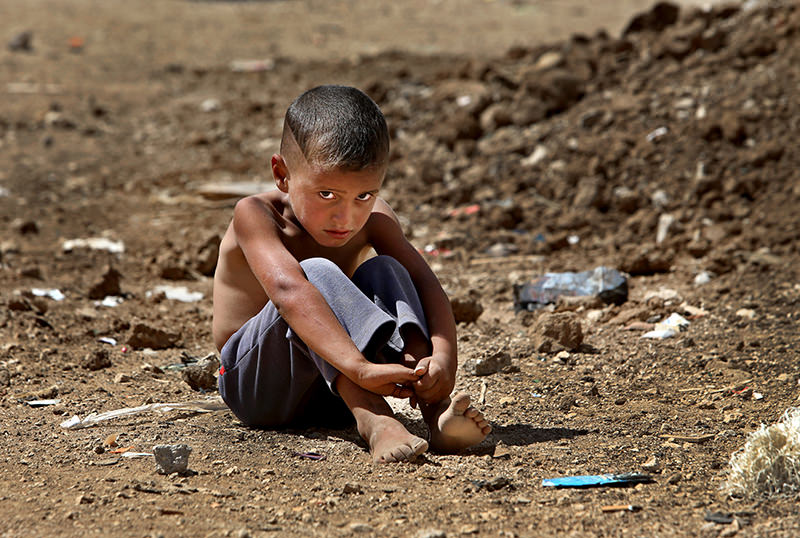 In this Wednesday, Sept. 11, 2013 file photo, A Syrian refugee boy sits on the ground at a temporary refugee camp, in the eastern Lebanese Town of Al-Faour. (AP Photo)