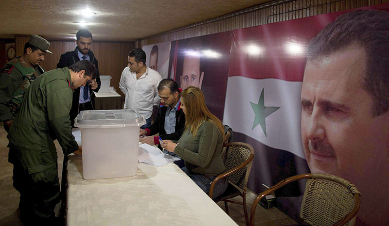 Syrian policemen cast their votes at a polling station during the parliamentary election in Damascus, Syria, Wednesday, April 13, 2016 (AP Photo)