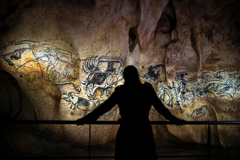 This file photo taken on April 8, 2015 shows a person looking at part of the full-scale reproduction of frescos found at the cave of Pont-D'Arc. (AFP Photo)